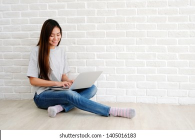 Young asian woman using laptop computer sitting in front of white brick wall background with copy space, people and technology, lifestyles, education, business concept