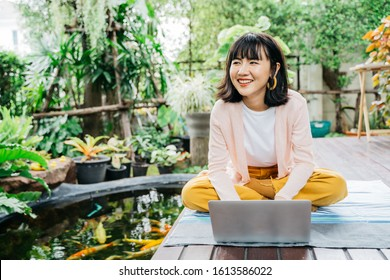Young asian woman using laptop for work and searching information on internet at home with happy. Technology and lifestyle people concept.