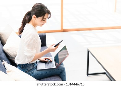 Young asian woman using a laptop pc and a smart phone in living room.