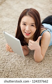 Young Asian woman using a pad PC in the home and show thumb.