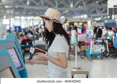 Young Asian woman using self check-in kiosks in airport. Technology in airport.