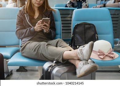 Young asian woman using smart phone while waiting for her flight at the airport