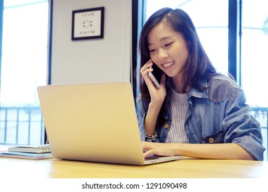 Young asian woman using smart phone and laptop computer with smiling, happy and relax emotion in bed room background, people on phone, working from home, lifestyle