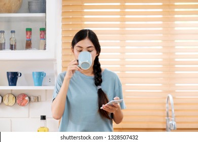 Young asian woman using smart phone while drinking coffee in kitchen background, people and technology, lifestyle