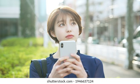 Young asian woman using a smart phone on the street.
