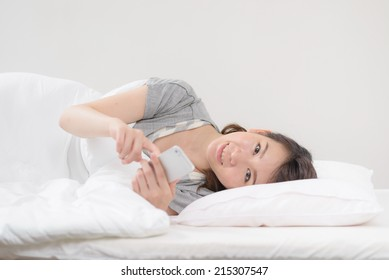 Young Asian woman using a smart phone on a bed.