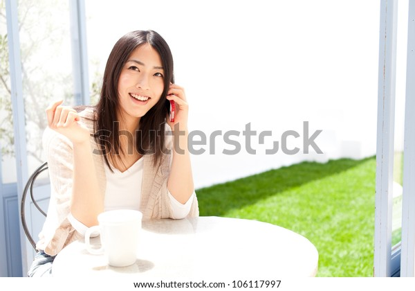 a young asian woman using smart phone in cafe
