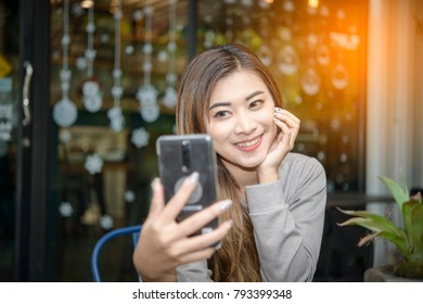 Young Asian woman using smartphone for browsing internet, personal chat, and social media in coffee shop on weekend. Vacation lifestyle in cafe with vintage filter effect. chilling in cafe and drinkin