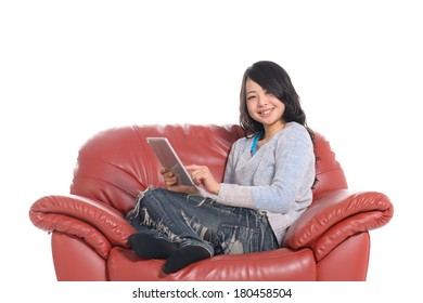 Young Asian woman using tablet PC on armchair, isolated on white background.