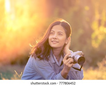 young Asian woman with vintage camera take photo in park travel concept