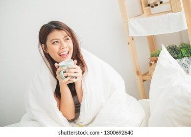 Young Asian woman wake up drinking coffee in bedroom in morning, Asian woman lifestyle concept