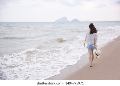 young asian woman walk on the beach in Thailand
