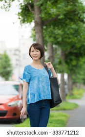 Young Asian woman walking on a city street.