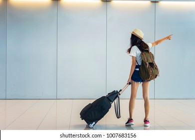Young asian woman walking and pulling the suitcase in airport.Travel concept.