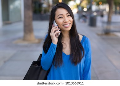 Young Asian woman walking talking on cellphone