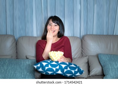 Young asian woman watching television suspense movie or news looking happy and funny and eating popcorn late night at home living room couch.