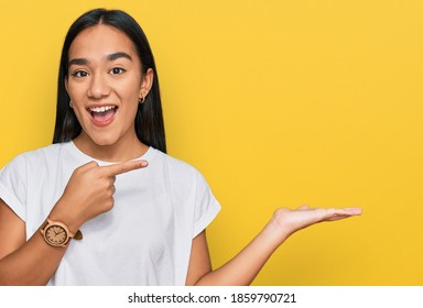 Young asian woman wearing casual white t shirt amazed and smiling to the camera while presenting with hand and pointing with finger.