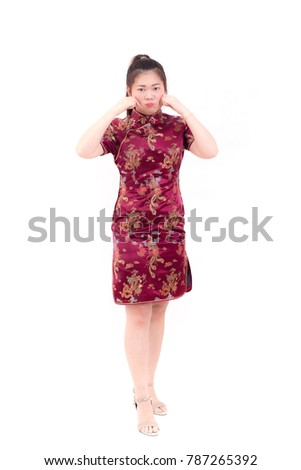 7008cc041 Young asian woman wearing chinese dress traditional cheongsam with pinching  her cheeks and pretend smile.