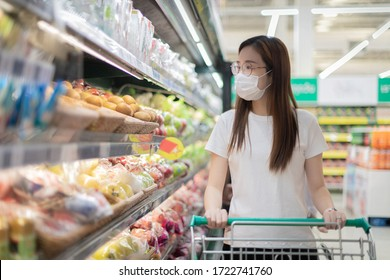 Young Asian woman wearing disposable medical mask shopping in the supermarket . during the Coronavirus COVID-19 pandemic.