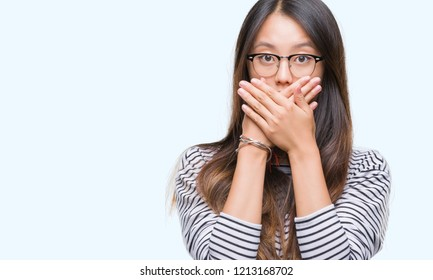 Young asian woman wearing glasses over isolated background shocked covering mouth with hands for mistake. Secret concept.