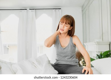 Young asian woman wearing gray clothes on bed with neck pain.Acute Inflammation in a woman nape. holding hand to back neck ,Health care concept
