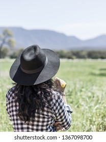 Young asian woman wearing a hat looking out over the fields of the Grampians whilst holding a flower.