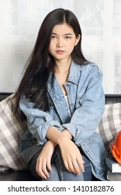 young asian woman wearing jeans jacket in studio