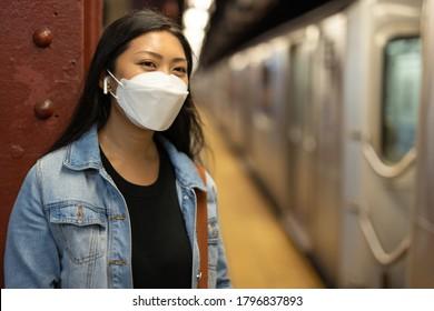 Young Asian woman wearing a mask at subway platform