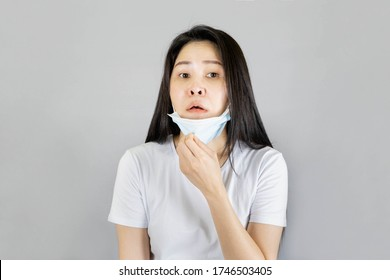 Young Asian woman wearing medical face mask and white t shirt her hands pull the mask down Inconvenient breathing, feeling uncomfortable isolated on gray background,health care concept