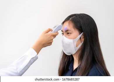 Young Asian woman wearing N95 mask, getting her temperature check - health concept