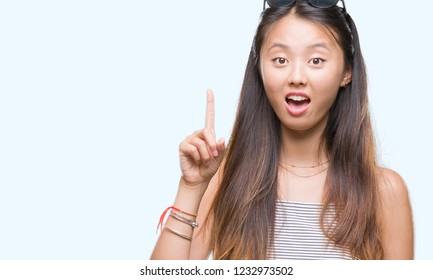 Young asian woman wearing sunglasses over isolated background pointing finger up with successful idea. Exited and happy. Number one.