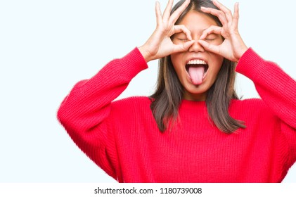 Young asian woman wearing winter sweater over isolated background doing ok gesture like binoculars sticking tongue out, eyes looking through fingers. Crazy expression.