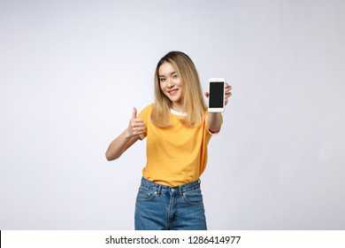 Young Asian woman wearing in yellow shirt is showing thumb up sign on white background, holding mobile phone, smiling,