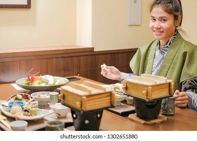 young Asian woman wearing Yukata with Japanese Dinner set and appetizer on wooden table in Traditional ryokan resort at Kawaguchiko lake, Yamanashi, Japan