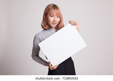 Young Asian woman with white blank sign on gray background
