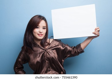 Young Asian woman with white blank sign on blue background