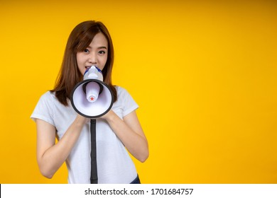 Young Asian woman in white casual t-shirt looking aside, scream in megaphone isolated on bright yellow wall background in studio. People lifestyle concept. Mock up copy space