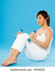 A young Asian woman in white holding small dumbbells on blue background