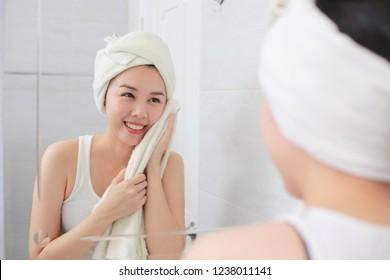 Young asian woman wiping her face with towel in bathroom.