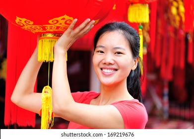 young asian woman wishing you a happy chinese new year with red lantern
