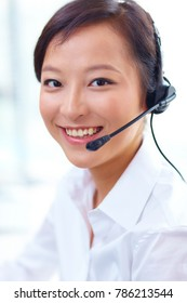 young asian woman working in front of computer with headset in the call centre