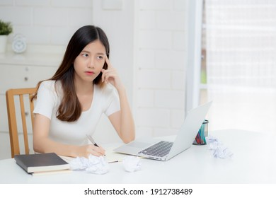 Young asian woman working with laptop computer think idea project and paper crumpled having problem on table at home, girl using notebook with frustrated and trouble, business and freelance concept.