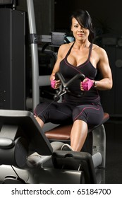 Young asian woman working out on rower in gym