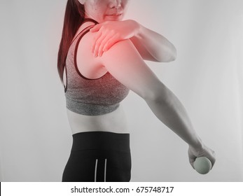 Young Asian woman in workout cloth holding hand and  having Shoulder pain with red focus dot on isolated background. concept of health care, view from rear people.