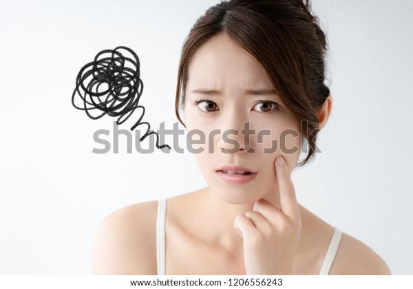 肌を気にするアジアの若い女性。
