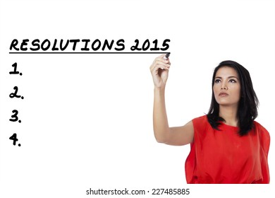 Young asian woman writes her resolutions list in 2015, isolated over white background