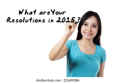 Young asian woman writes a question of resolutions in 2015