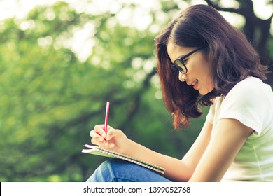 Young Asian woman writing on notebook or diary at outdoor