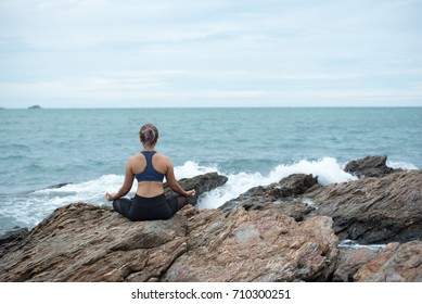 Young asian woman yoga and meditation on the stone at the sea beach, healthy lifestyle and fitness concept.