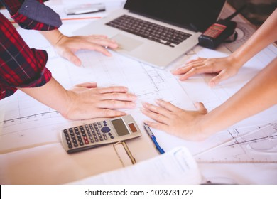 Young asian women architect working on blueprint in the office,engineering work with blueprint,using calculator and laptop,teamwork,construction concept.